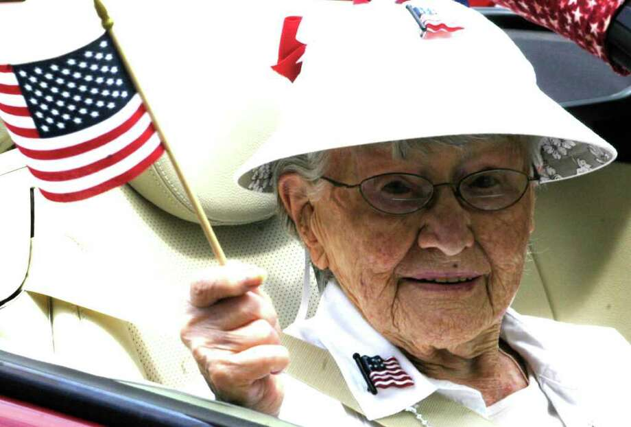 "SPECTRUM/100-year-old Dorothy ""Dot"" Clark proudly waves the Stars and Stripes as she rides Sunday along Route 39 North into the village center as the Grand Marshal of the Sherman Memorial Day parade. May 29, 2011 Photo: Norm Cummings / The News-Times"