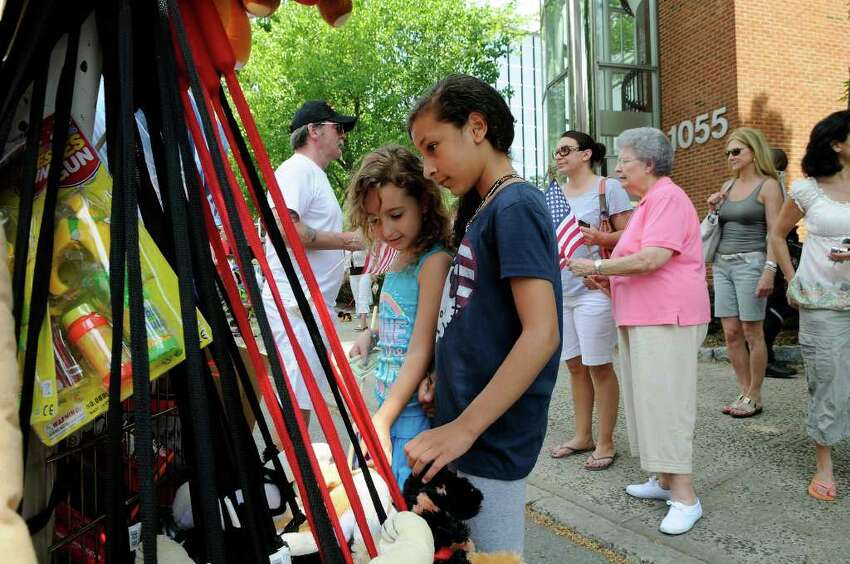 Cousins Laura Scandizzo, Keller TX, and Giana Scandizzo, Stamford, peruse the festive novelties at the Memorial Day parade in downtown Stamford, CT on Sunday May 29, 2011.