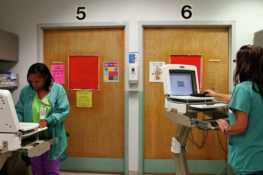 Princess Hope, RN, left, working next to Lily Wildberger, RN, right, came up with the idea for Three at Three, where staff and patients, if they want to get involved, wipe down three things at three a.m. and three p.m. in the Bone Marrow Transplant program at the Audie L. Murphy Veterans Hospital in San Antonio on Wednesday, April 27, 2011. Signs hang on walls and doors as hand washing reminders and alerting different levels of precautions that need to be taken for specific patients, as in the pink sign on the door, left. LISA KRANTZ/lkrantz@express-news.net Photo: LISA KRANTZ, Lisa Krantz/Express-News / SAN ANTONIO EXPRESS-NEWS