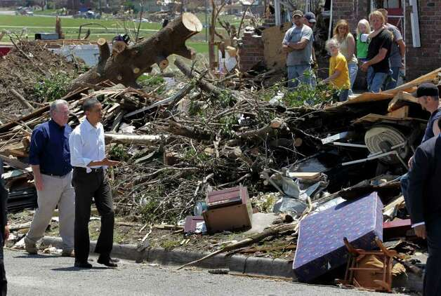 President Barack Obama reaches out to residents while viewing damage from the tornado that devastated Joplin, Mo., Sunday, May 29, 2011.  He is joined by Missouri Gov. Jay Nixon.  (AP Photo/J. Scott Applewhite) Photo: J. Scott Applewhite