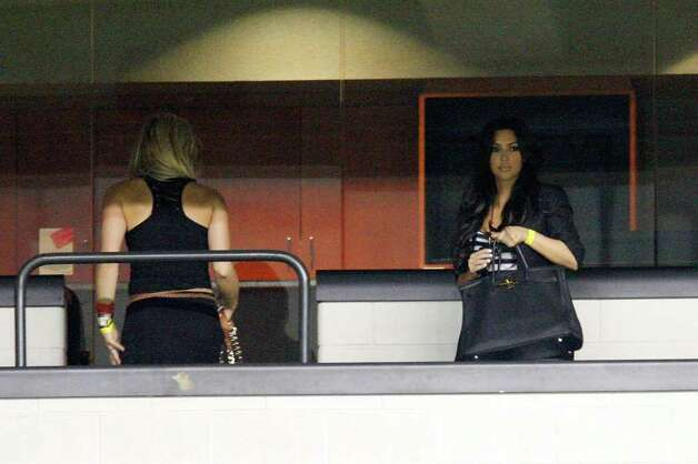 COWBOYS -- Dallas Cowboys wide receiver Miles Davis' girlfriend Kim Kardashian, right, and quarterback Tony Romo's girlfriend Candice Crawford leave a suite as the team practices at the Alamodome, Sunday, August 1, 2010.  Kardashian is a television star while Crawford is a television sports reporter. JERRY LARA/glara@express-news.net Photo: JERRY LARA, San Antonio Express-News / glara@express-news.net