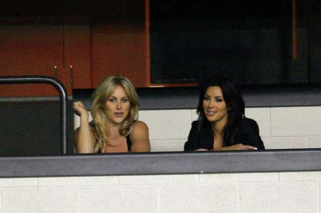 COWBOYS -- Dallas Cowboys wide receiver Miles Davis' girlfriend Kim Kardashian, right, and quarterback Tony Romo's girlfriend Candice Crawford sit together in a suite as the team practices at the Alamodome, Sunday, August 1, 2010.  Kardashian is a television star while Crawford is a television sports reporter. JERRY LARA/glara@express-news.net Photo: JERRY LARA, San Antonio Express-News / glara@express-news.net