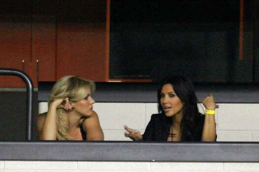 COWBOYS -- Dallas Cowboys wide receiver Miles Davis' girlfriend Kim Kardashian, right, and quarterback Tony Romo's girlfriend Candice Crawford sit together in a suite as the team practices at the Alamodome, Sunday, August 1, 2010.  Kardashian is a television star while Crawford is a television sports reporter. JERRY LARA/glara@express-news.net Photo: JERRY LARA, Express-News / glara@express-news.net