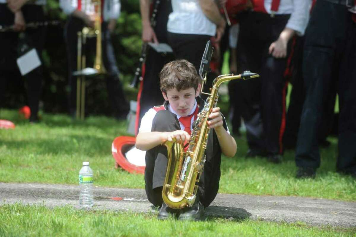 Trevor Kelly, 13, sits with his saxaphone at the ceremony after the Old Greenwich Memorial Day Parade down Sound Beach Avenue on Monday, May 30, 2011.