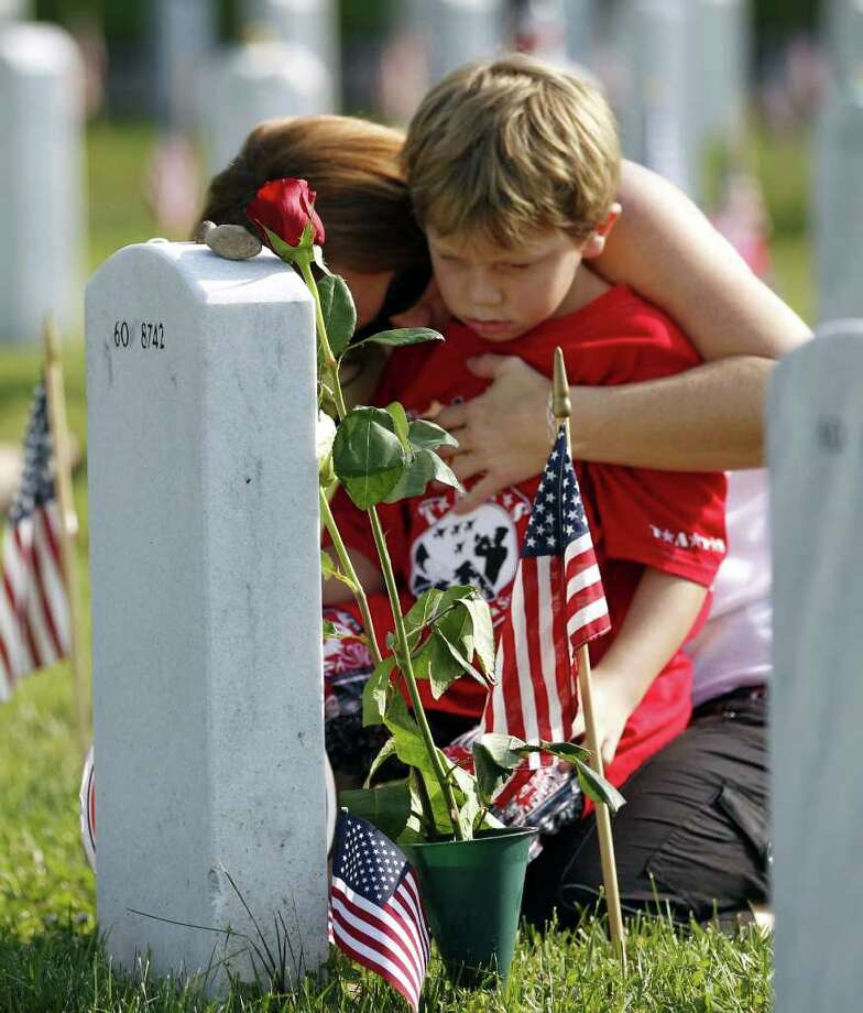Trisha Lawton and her son Caden prays over the grave of husband and father, Marine Capt. Garrett T. Lawton on Memorial Day Monday in Arlington National Cemetery's Section 60, which was visited by President Barack Obama Monday.  Lawton, 31, of of Charleston, W.Va., in 2008 during Operation Enduring Freedom. Photo: AP