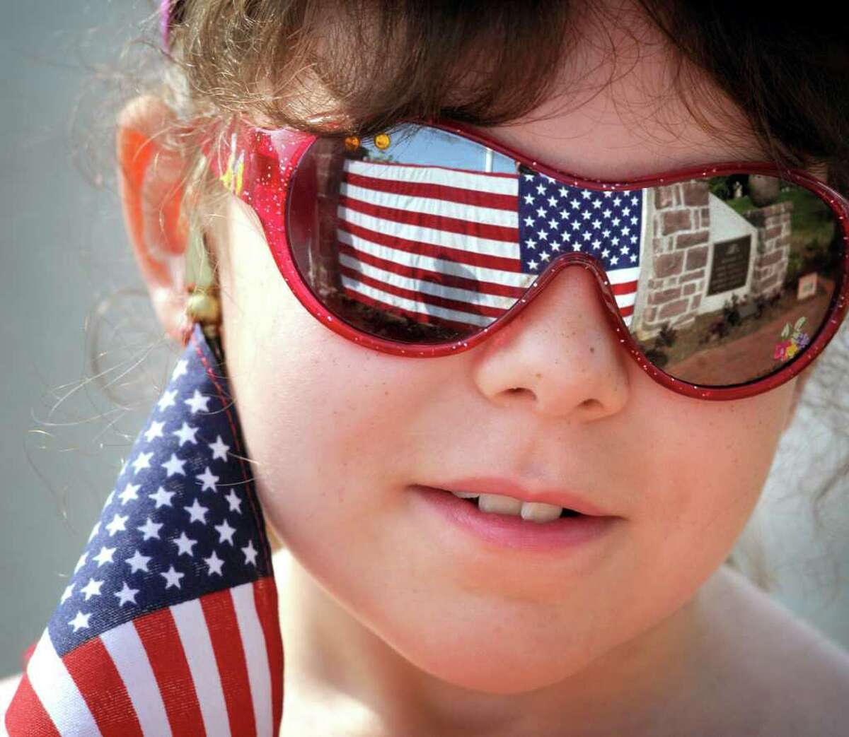 Molly Fasnacht,7, from Schoeneck, Pa. attends a Memorial Day service on Monday. Americans from Washington to California marked Memorial Day with parades, barbecues and somber moments of reflection.