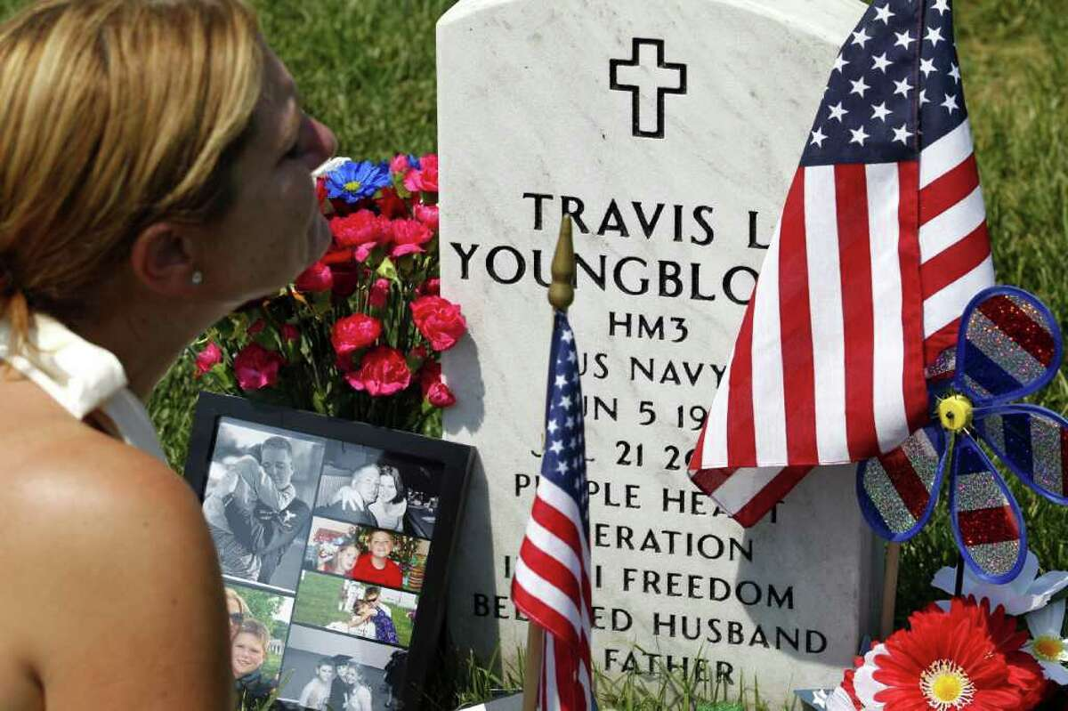 Laura Youngblood prays over the grave of her husband Travis L. Youngblood at section 60 in Arlington National Cemetery, Monday.