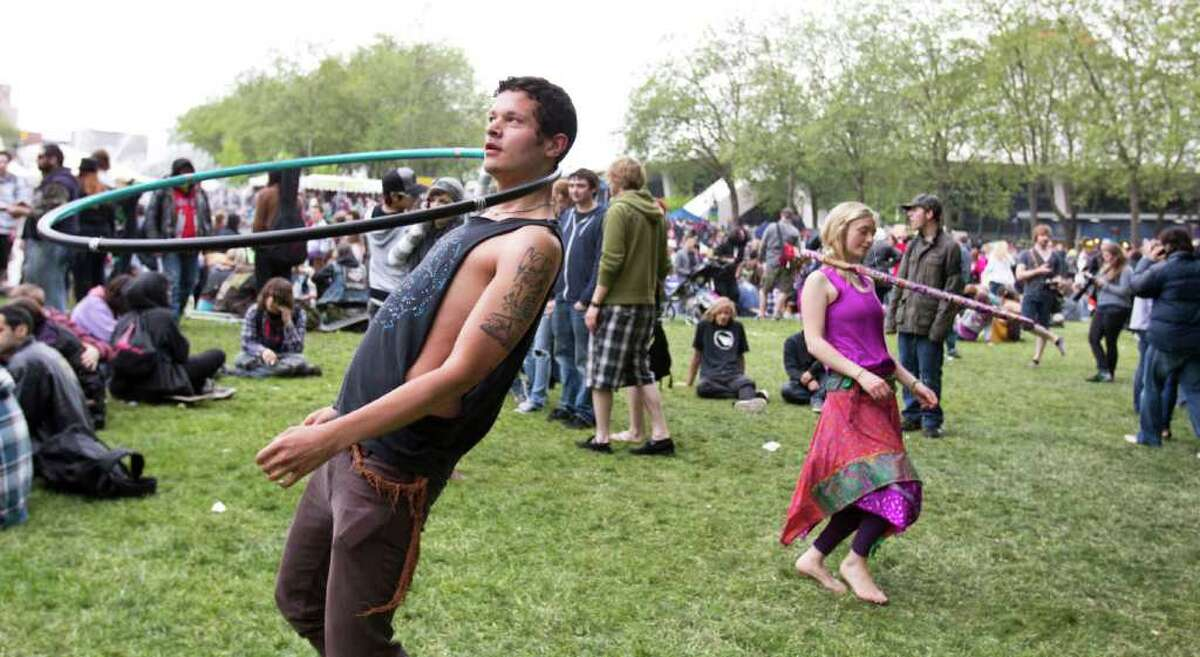 Kyle Taylor and Lori Dickerson hoop to the sounds of live drums, Sunday, at the Northwest Folklife Festival.
