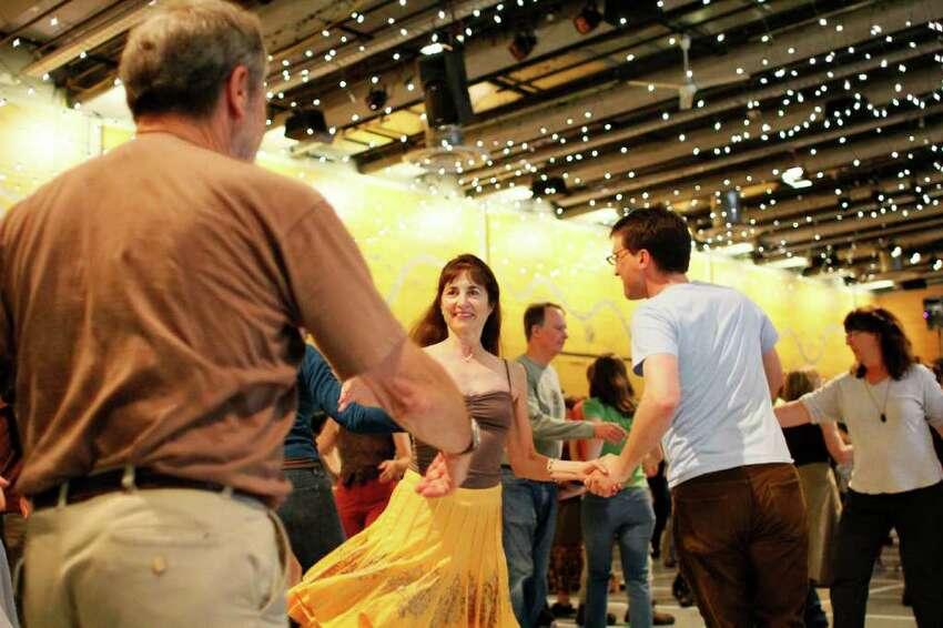 Bruce Sigloh, left, and Elizebeth Bennett, middle, dance at the Northwest Folklife Festival.