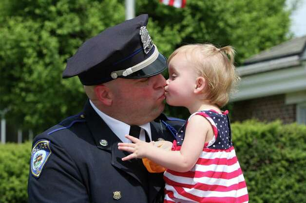 Darien Police Officer Dan Ehret gets a kiss from his daughter, Ellie, at Monday's Memorial Day Parade. Kristen Riolo for the Darien News Photo: Contributed Photo / Darien News