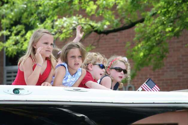 Children from the Darien Sail & Power Squadron wave to the crowd from a boat during Darien's annual Memorial Day Parade Monday morning. Kristen Riolo for the Darien News Photo: Contributed Photo / Darien News
