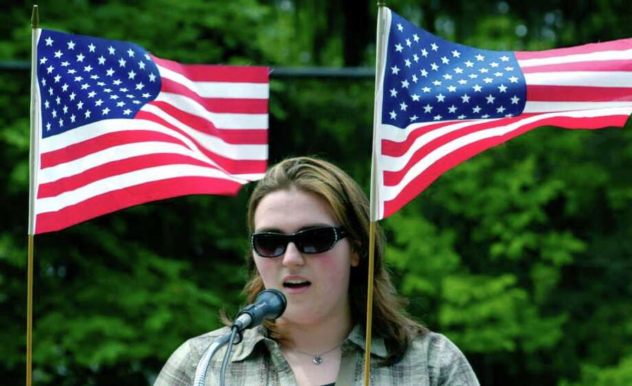 """SPECTRUM/As the Stars and Stripes wave in Sunday's breeze, Meghan Tanner reads Abraham Lincoln's """"Gettysburg Address"""" during the Warren Memorial Day ceremony. May 29, 2011 Photo: Norm Cummings / The News-Times"""