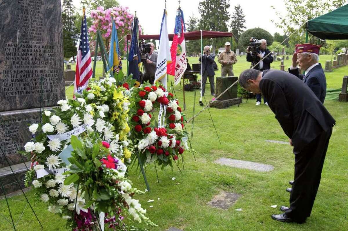 Guests and veterans pay their respect at the Nisei Veteran memorial at Lake View Cemetery.