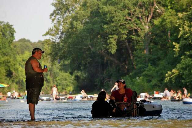 Brett Graves, of San Antonio, talks with his girlfriend, Angelica Reyes, right, both of San Antonio, and Dollie Lagunas of New Braunfels, as they relax in the Comal River in New Braunfels on Saturday, May 28, 2011. LISA KRANTZ/lkrantz@express-news.net Photo: LISA KRANTZ, Lisa Krantz/Express-News / SAN ANTONIO EXPRESS-NEWS