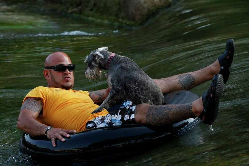 Tubers, including Jesse Ozuna, of San Antonio, with his dog, Zoe, enjoy the Comal River in New Braun