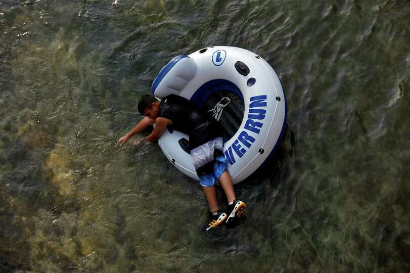 Tubers, including Adam Martinez, 13, of San Antonio, enjoy the Comal River in New Braunfels on Satur