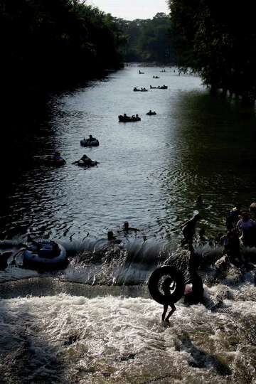 Tubers, including Mariah Rodriguez, 9, of New Braunfels, bottom/right, enjoy the Comal River in New