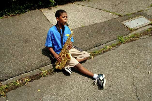Tyquan Green (9) from the Side by Side Community School plays his sax on the curb after marching in the Norwalk, Conn. Memorial Day Parade on Monday May 30, 2011. Photo: Dru Nadler / Stamford Advocate Freelance
