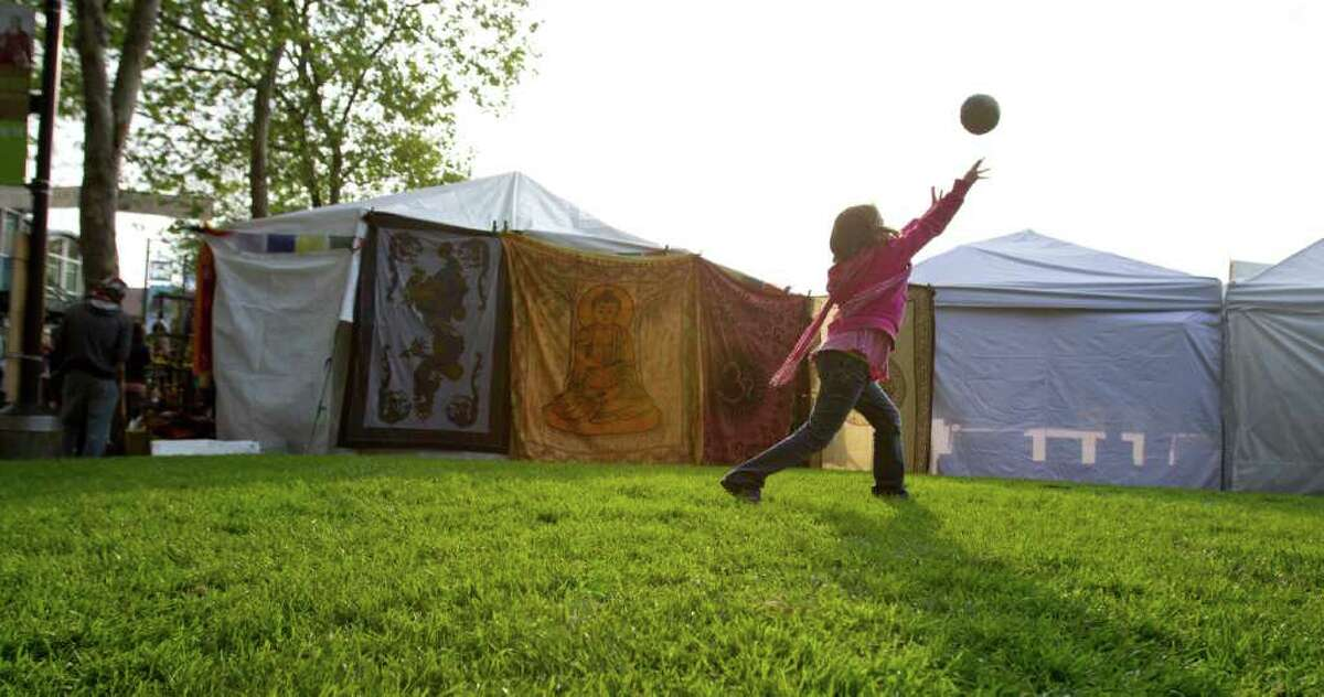 This 8-year-old enjoys a game of catch with her uncle at the Northwest Folklife Festival on Monday.