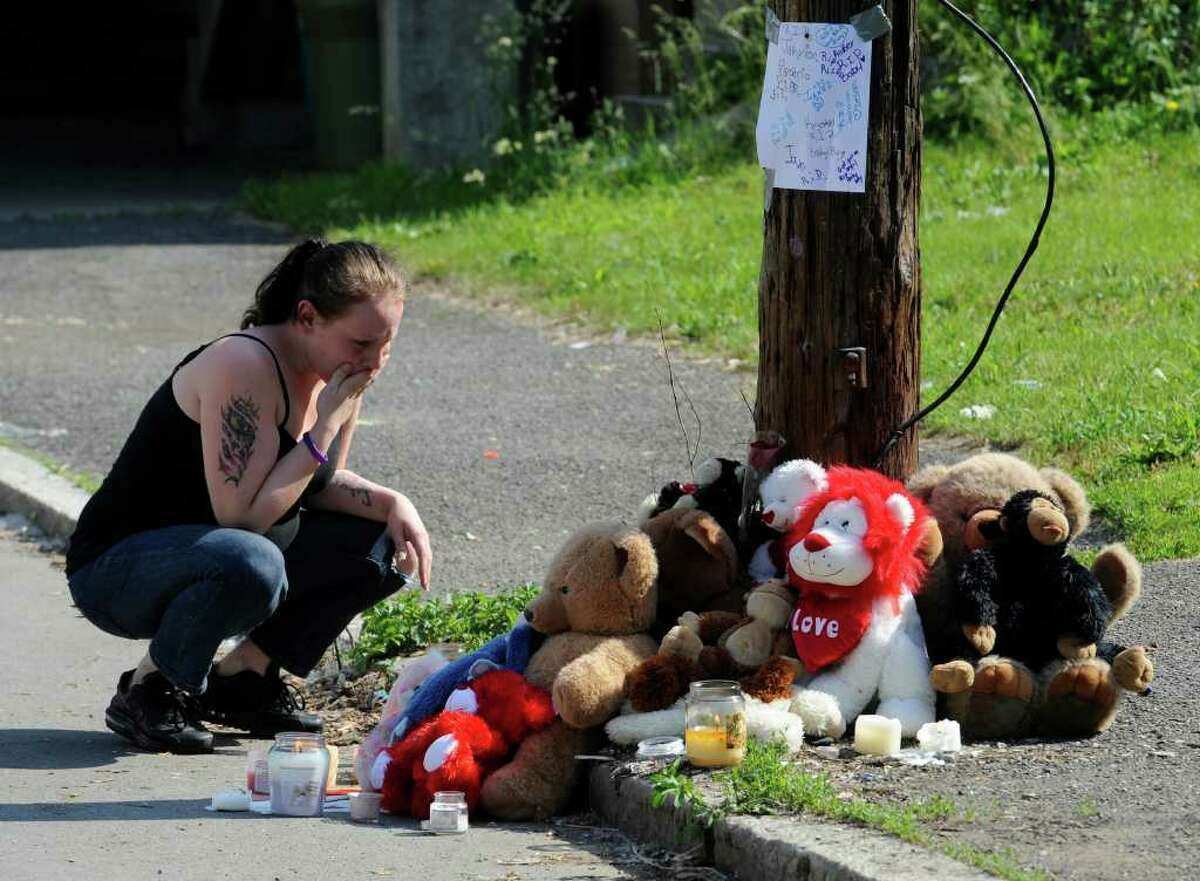 A neighbor kneels at a memorial Tuesday for Jahvion Perez, 6, on 10th Street, just north of Rensselaer Street in Troy. Jahvion was killed by Roy Sanders of Troy in a hit-and-run accident on Memorial Day. (Skip Dickstein / Times Union )