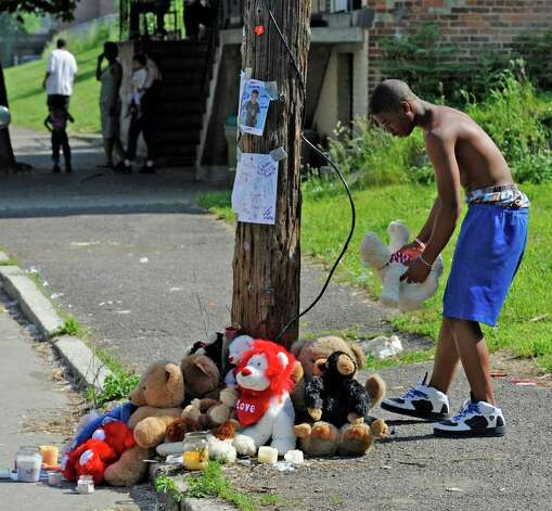 Ahlaumion Hall, 14, puts a teddy bear at a memorial on 10th Street just north of Rensselaer Street in Troy for Jahvion Perez after the 6-year-old was killed by Roy Sanders in a hit-and-run accident on Memorial Day. (Skip Dickstein / Times Union ) Photo: SKIP DICKSTEIN / 2008
