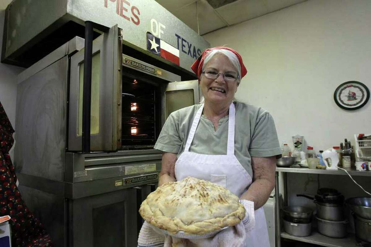Janie Bailey pulls one of her signature apple pies from the oven at Janie's Pie Factory, which specializes in fruit pies, cobblers and casseroles.