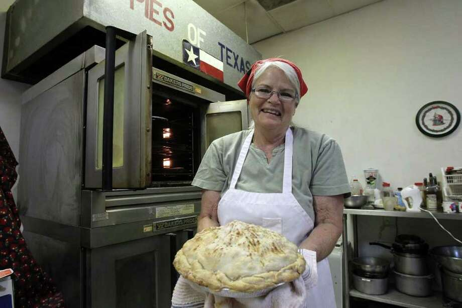 Janie Bailey pulls one of her signature apple pies from the oven at Janie's Pie Factory, which specializes in fruit pies, cobblers and casseroles. Photo: JOHN DAVENPORT, SAN ANTONIO EXPRESS-NEWS / SAN ANTONIO EXPRESS-NEWS (Photo can be sold to the public)