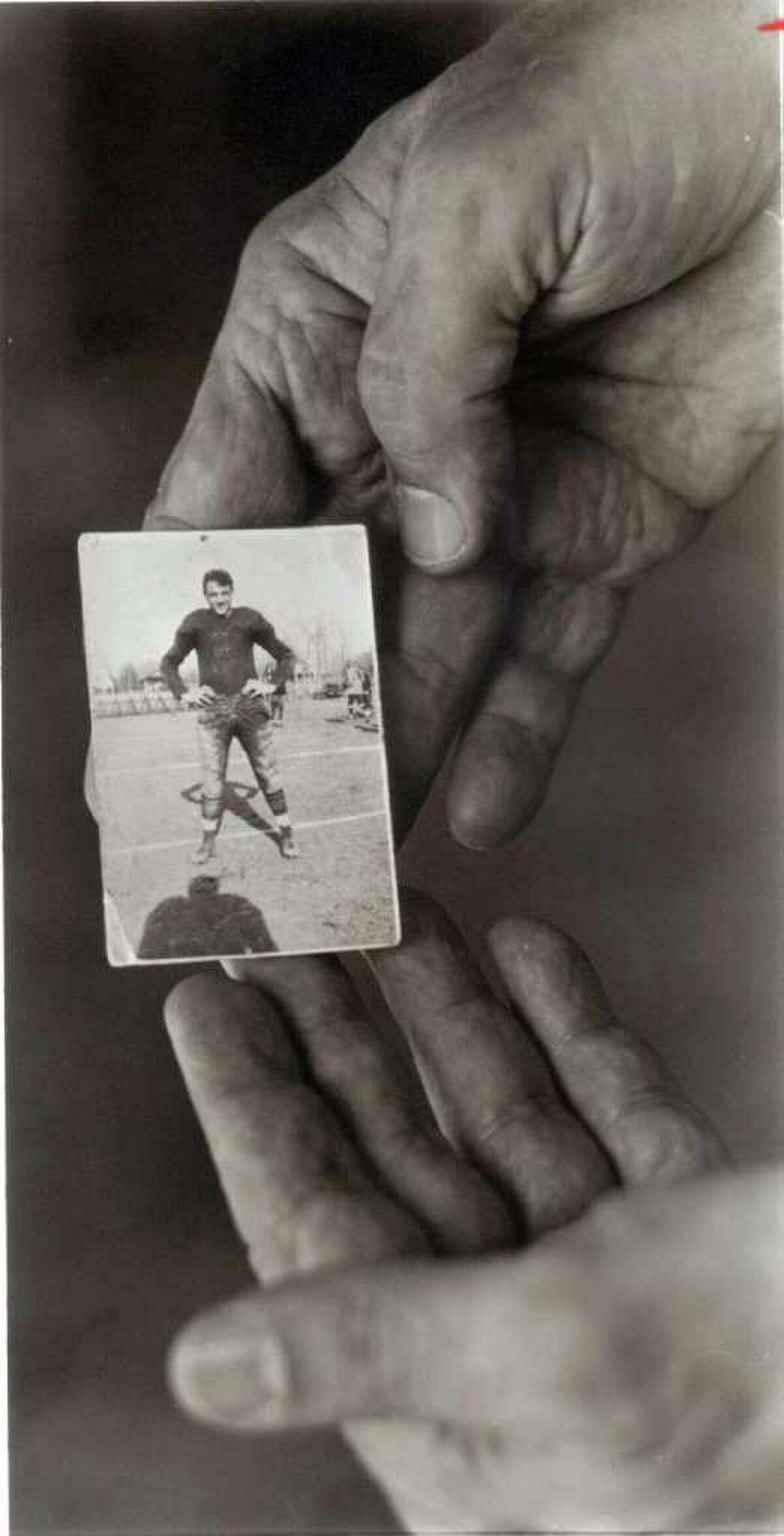 In a photo from 1991, Andy Robustelli holds a photo of himself in 1943 when he played football for Stamford High School. Robustelli, a NFL Hall of Famer, died Tuesday at 85.