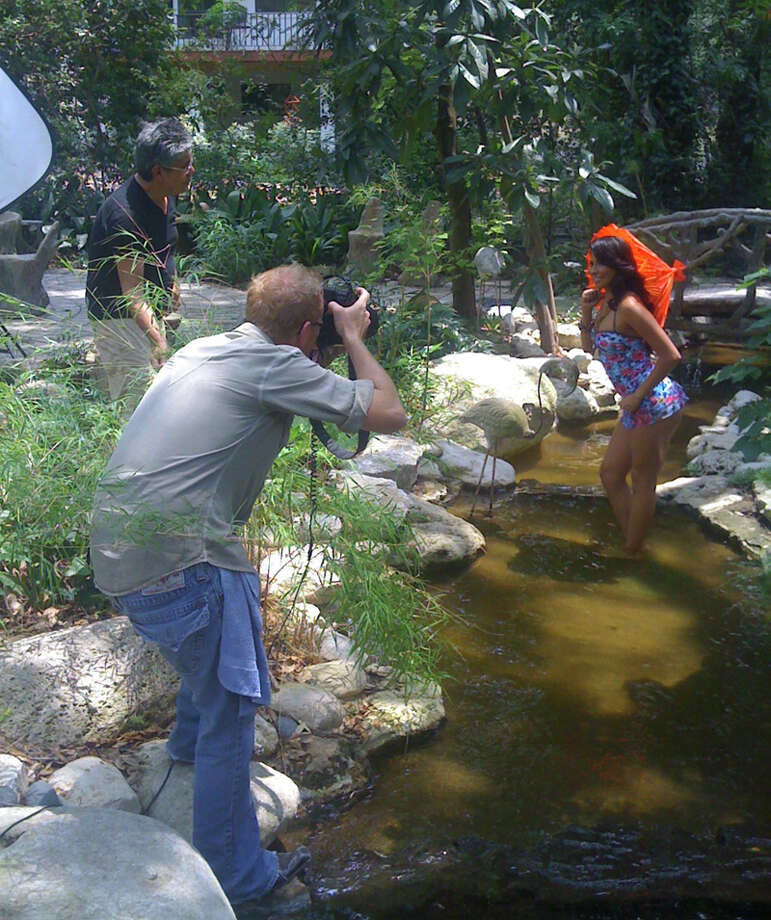 Photographer Kevin Geil perches on the edge of the creek for a perfect angle while fashion writer Michael Quintanilla holds a limb out of the shot. TERRY SCOTT BERTLING / EXPRESS-NEWS