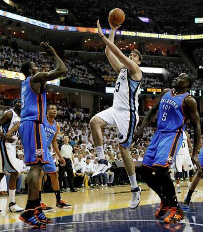 Memphis Grizzlies center Marc Gasol (33), of Spain, shoots against Oklahoma City Thunder forward Serge Ibaka (9) and Kendrick Perkins (5) during the first half of Game 3 of a second-round NBA basketball series on Saturday, May 7, 2011, in Memphis, Tenn. (AP Photo/Mark Humphrey) Photo: Mark Humphrey, STF