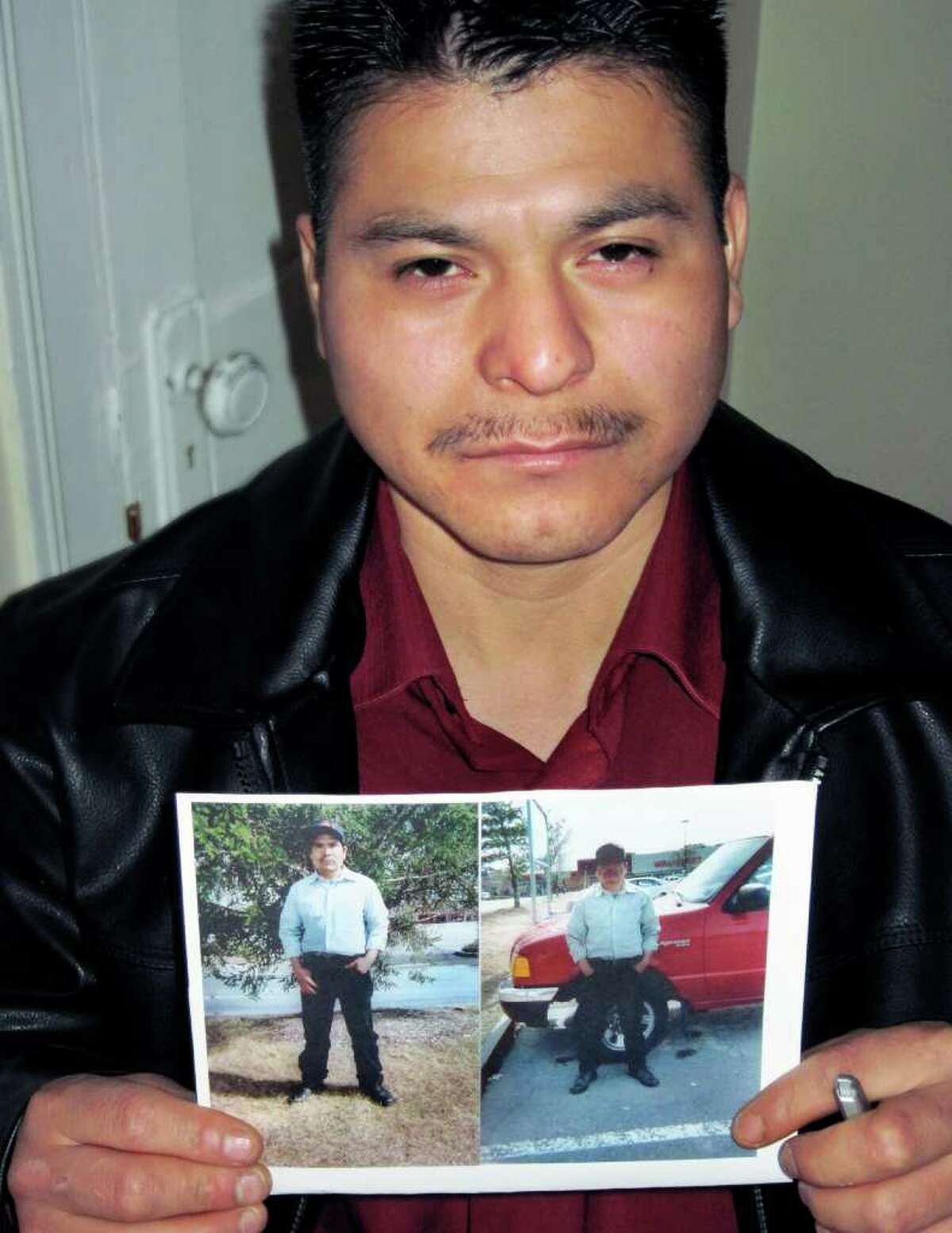 Maurilio Garcia holds photographs of his brother-in-law Marcos DeJesus Alvarez, who was shot and killed by a sheriff's deputy on March 20, 2010. Garcia and Alvarez shared an apartment on Central Avenue in Albany with other undocumented Mexicans. (Paul Grondahl / Times Union)