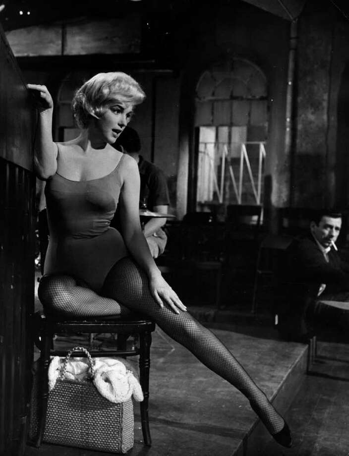 Monroe stretches her leg under the watchful eye of Yves Montand on the set of 'Let's Make Love' in 1960. Photo: L. J. Willinger, Getty Images / Hulton Archive