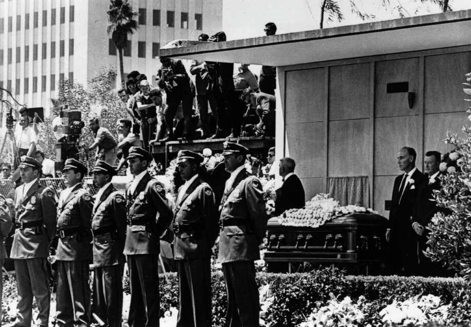 Detectives from the Pinkerton Agency guard Monroe's coffin during her funeral on August 8, 1962 in Westwood Memorial Park, Hollywood. Photo: Keystone, Getty Images / Hulton Archive