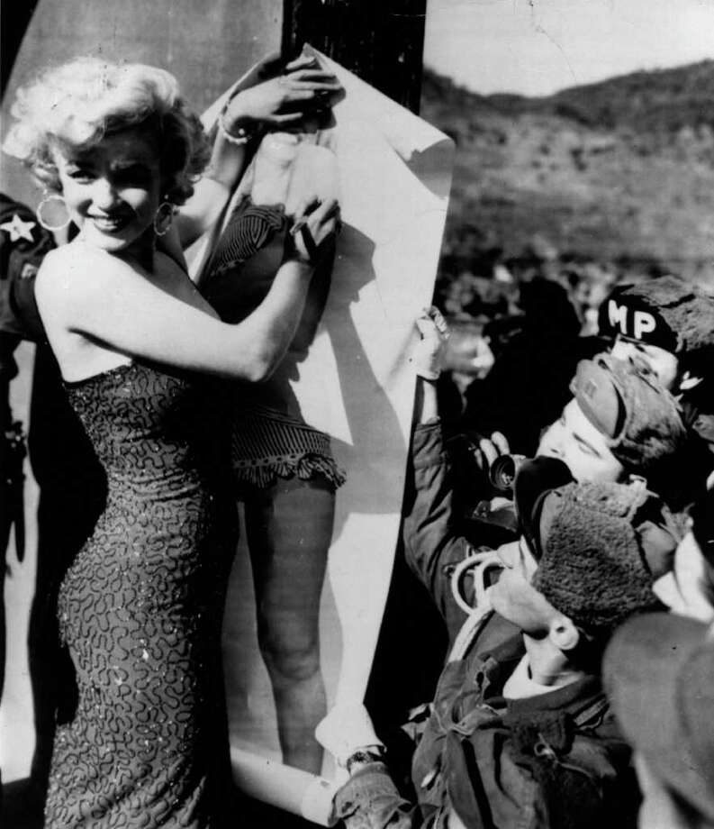 Monroe autographs a full-sized picture of herself in a polka dot bikini (from the film 'Love Nest') for the troops, circa 1955. Photo: Hulton Archive, Getty Images / Hulton Archive