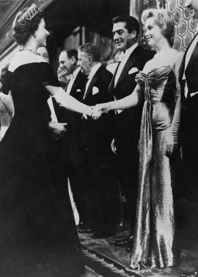Queen Elizabeth II shakes hands with Monroe at a Royal Film Performance of 'The Battle of the River Plate' at the Empire Theatre, Leicester Square, London, on October 29, 1956. Photo: Keystone, Getty Images / Hulton Archive