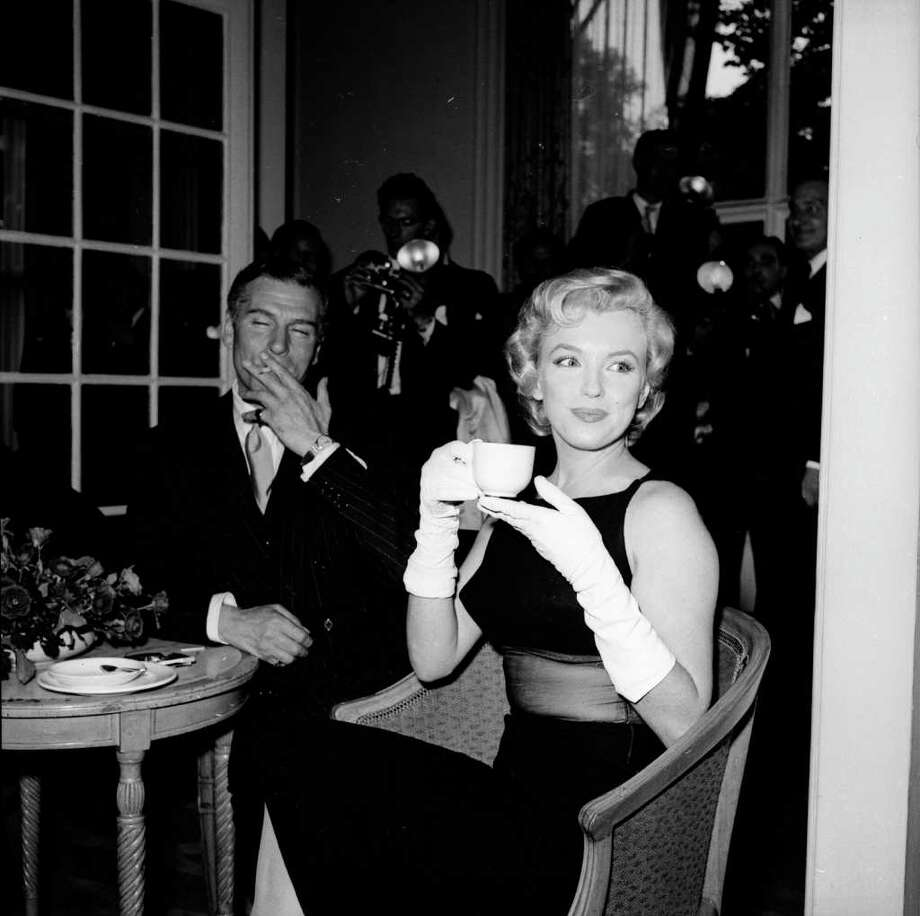 Monroe sits next to British thespian Laurence Olivier at a press conference at the Savoy Hotel, London, in July 1956. Photo: Harry Kerr, Getty Images / Hulton Archive