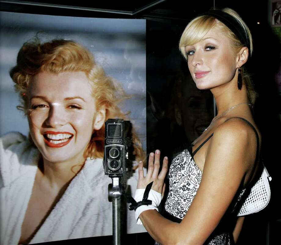 "Actress Paris Hilton poses with a photograph of Monroe at the unveiling of the new exhibit ""Idols of Gay Hollywood"" at The Hollywood Museum on June 8, 2006 in Hollywood, California. Photo: David Livingston, Getty Images / 2006 Getty Images"