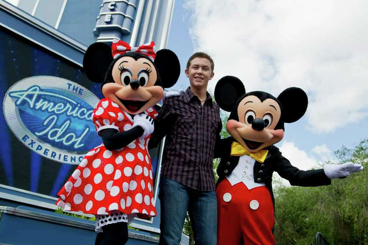 """Newly crowned """"American Idol"""" Scotty McCreery poses with Mickey and Minnie Mouse in front of """"The American Idol Experience"""" attraction at Disney's Hollywood Studios in Lake Buena Vista, Florida. McCreery was honored in a parade at the Disney theme park and performed his new song """"I Love You This Big."""" On Wednesday, the 17-year-old singer was crowned the new """"American Idol"""" on the season finale, which was viewed by an estimated 29.3 million people."""