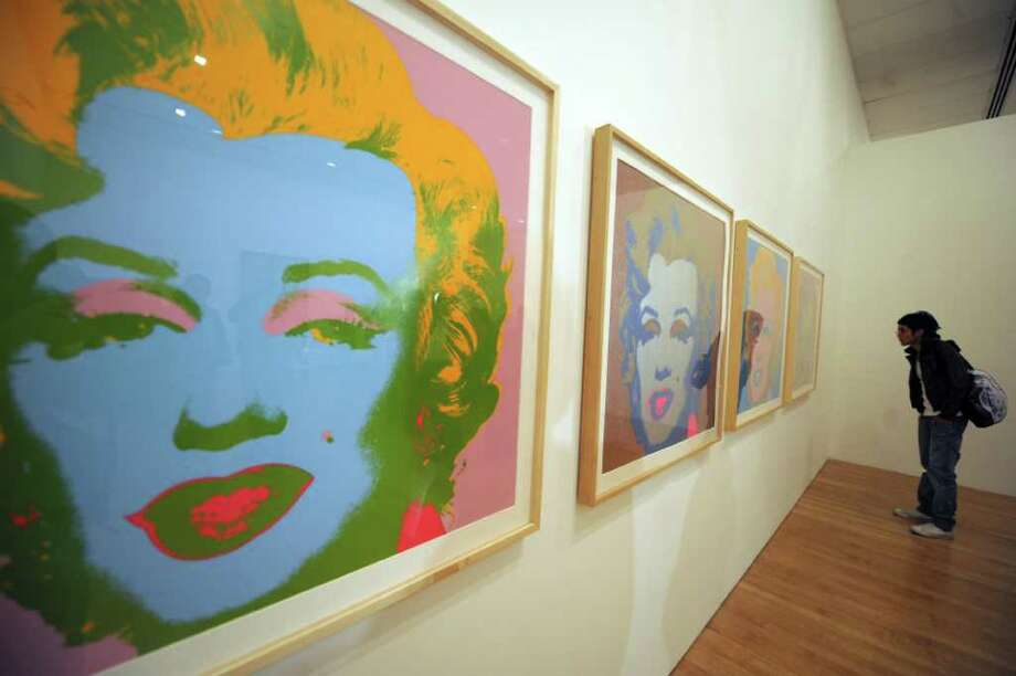 "A visitor looks at Andy Warhol's paintings from the series ""Marilyn Monroe, 1969"" in Bogota on June 18, 2009, in Bogota, Colombia. Photo: AFP/Getty Images"
