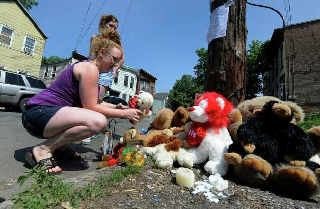 Cassondra Abrams, with her friend Amber Carbonneau, puts a teddy bear at a memorial  on 10th Street just north of Renssealer Street in Troy after  Jahvion Perez, 6, was killed by Roy Sanders in a hit-and-run accident on Memorial Day. (Skip Dickstein / Times Union) Photo: SKIP DICKSTEIN / 2008