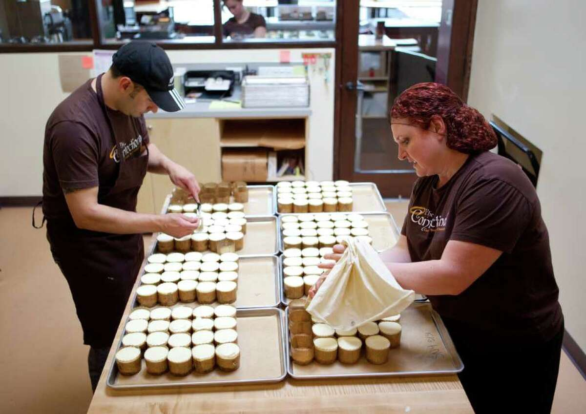 Owners Paul Verano and Destiny Sund work on some of thier creations in the kitchen at The Confectional on Tuesday, May 31, 2011 on Broadway in Capitol Hill.