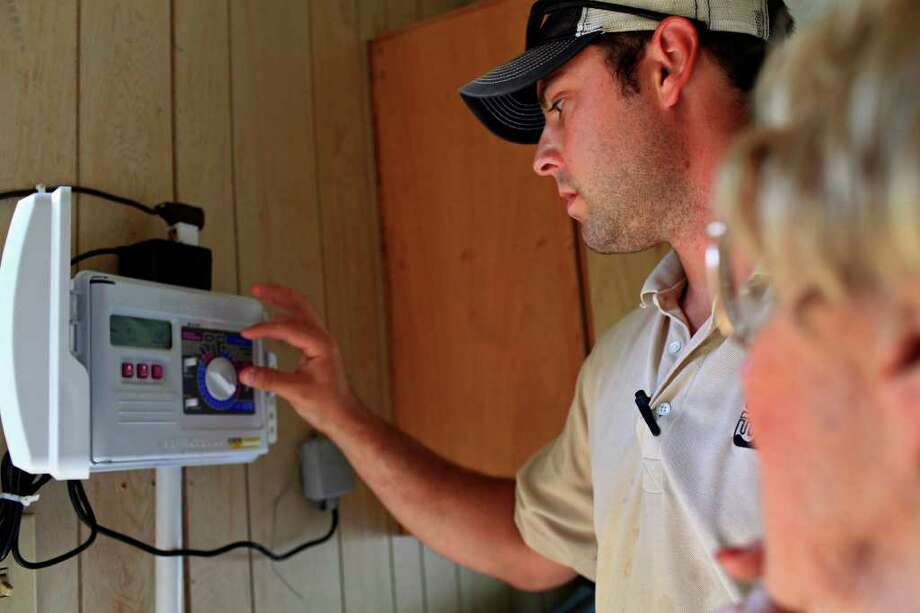 Darik Conner, a technical field investigator with San Antonio Water System, installs a backup battery for a sprinkler system controller for a homeowner and explains the details to her after finding the controller was set wrong and a lateral line leak in her sprinkler system at her home in San Antonio on Tuesday, May 31, 2011. LISA KRANTZ/lkrantz@express-news.net Photo: LISA KRANTZ, Lisa Krantz/Express-News / lkrantz@express-news.net