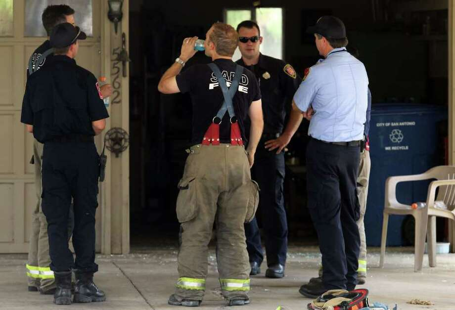 San Antonio firefighters stand under a carport at 5562 Aspen Valley where a man died after a fire broke out at his home Tuesday May 31, 2011. According to fire officials the man was in his 80s and smoking materials were found near where he was sitting. JOHN DAVENPORT/jdavenport@express-news.net Photo: John Davenport/Express-News