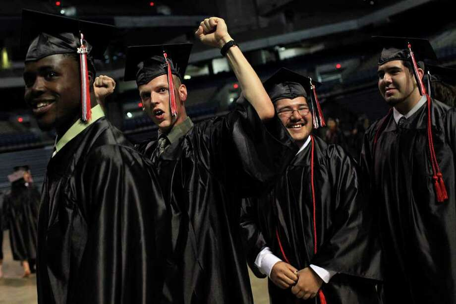 Wagner High's Aaron Michaels (second from left), cheers near Adam Miller (from left), Manuel Meza and Domingo Meza at graduation in the Alamodome. Michaels had to cope with autism and the loss of his grandparents, who cared for him. Photo: LISA KRANTZ, Lisa Krantz/Express-News / lkrantz@express-news.net
