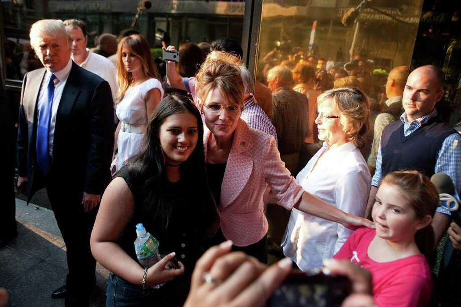 NEW YORK, NY - MAY 31:  Former U.S. Vice presidential candidate and Alaska Governor Sarah Palin (C), takes a picture with supporters while Donald Trump, left, waits, after leaving Trump Tower, at 56th Street and 5th Avenue, on May 31, 2011 in New York City.  Palin and Trump met for a dinner meeting in the city. Photo: Andrew Burton, Getty Images / 2011 Getty Images