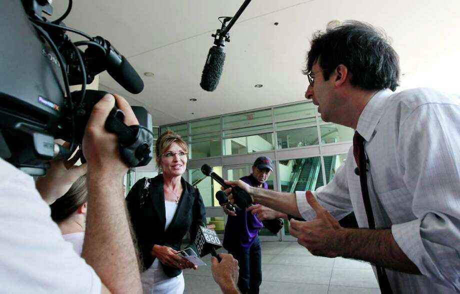 Former Alaska Gov. Sarah Palin, center, answers questions by Comedy Central reporter John Oliver outside the Hyatt Regency Hotel, Wednesday, June 1, 2011 in Jersey City, N.J. Photo: Julio Cortez, AP / AP