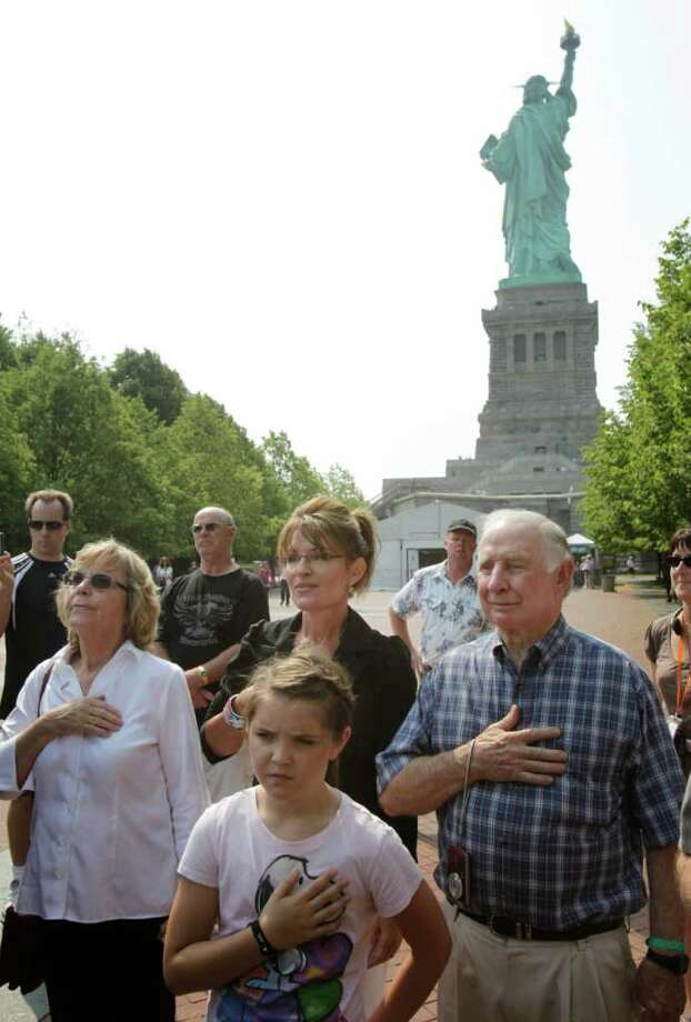 "Sarah Palin, center, her daughter Piper Palin, front, and her parents, Sally and Chuck Heath, pause as a band plays ""The Star-Spangled Banner""  during their visit to Liberty Island in New York, Wednesday, June 1, 2011. Photo: Seth Wenig, AP / AP"