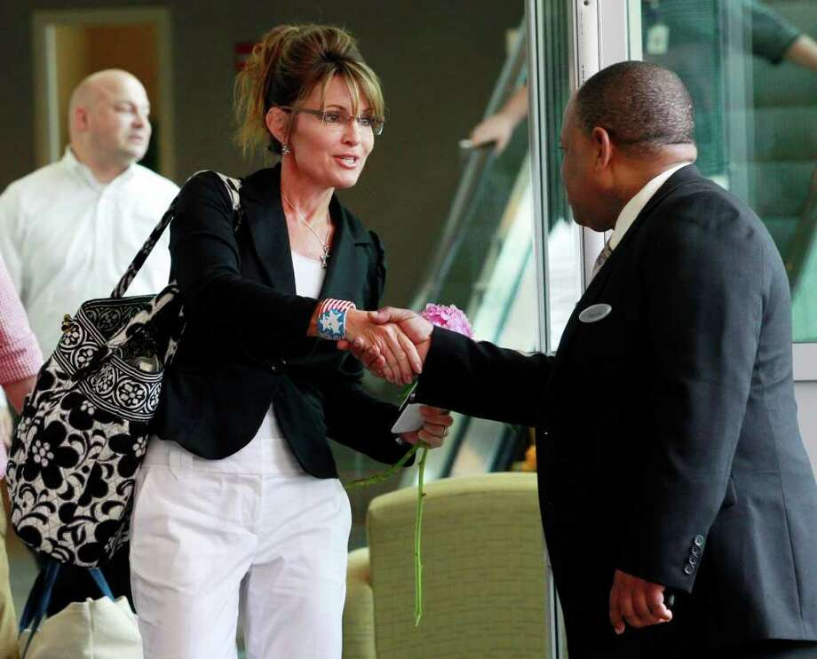 Former Alaska Gov. Sarah Palin, left, shakes the hand of an employee at the Hyatt Regency Hotel in Jersey City, N.J., while checking out of the hotel, Wednesday, June 1, 2011. Photo: Julio Cortez, AP / AP