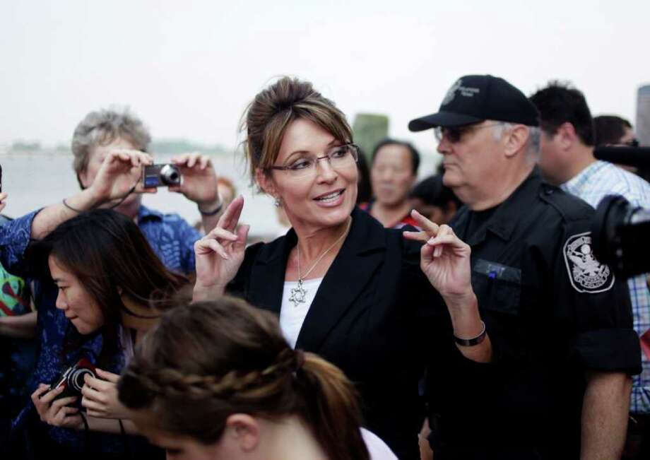 Former Alaska Gov. Sarah Palin talks to the media as she leaves Liberty Island in New York, Wednesday, June 1, 2011. Photo: Seth Wenig, AP / AP