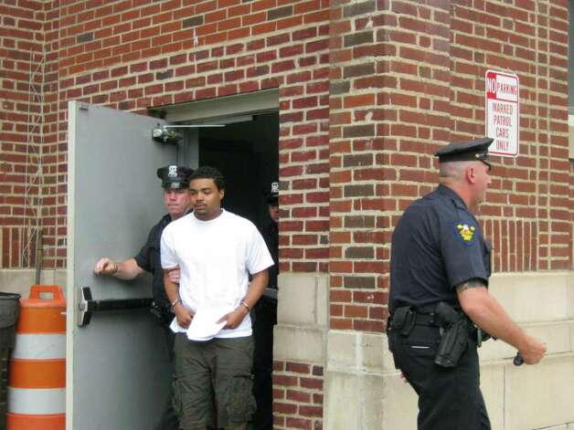Roy Sanders, 21, is escorted from the Troy police station following his arraignment. (Chelsea Diana / Special to the Times Union)